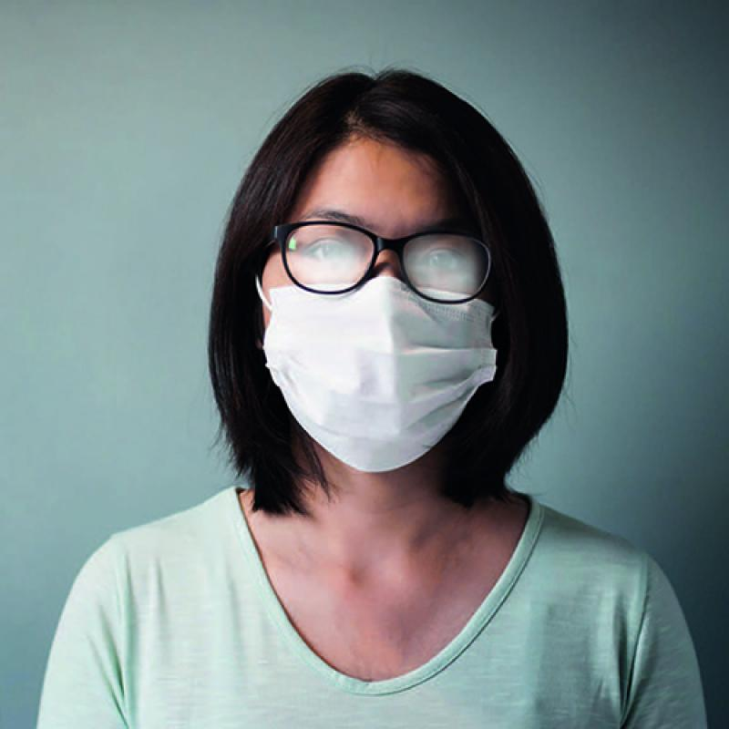 Woman wearing glasses on top of face mask