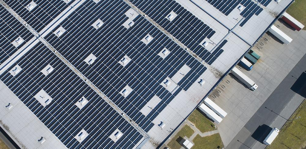 Large industrial building, solar panels and trucks - aerial view